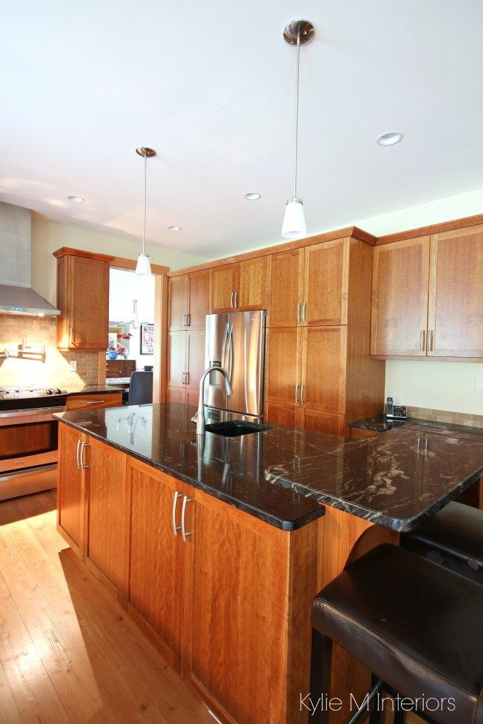 Kitchen design with island, black granite, cherry cabinets fir flooring, stainless steel appliances and raised eating bar