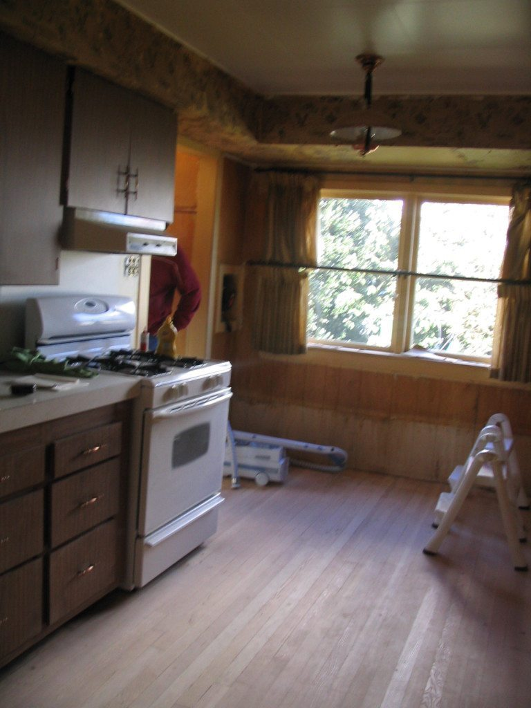 Old laminate cabinet kitchen with fir floors and wood panelling before update and remodel with paint