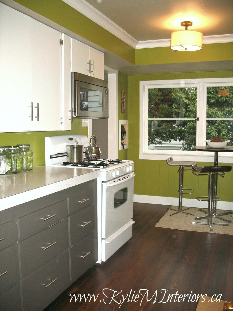 Old laminate kitchen cabinets painted with Benjamin Moore Cloud White, Amherst Gray. Dark fir stained wood floor and Forest Moss by Benjamin Moore paint color