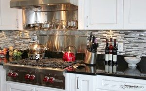 Beautiful chefs kitchen with white glazed cabinets, black granite, and stainless steel mosaic tile backsplash by Kylie M Interiors
