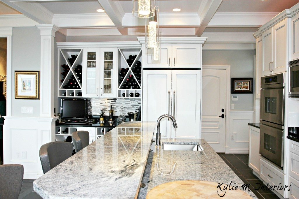 Marble island with raised bar top, wine bar station with white glazed cabinets, coffered ceilings and Benjamin Moore Stonington Gray walls. Design by Kylie M Interiors