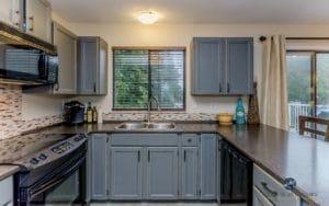 Oak cabinets Benjamin Moore Chelsea Gray. Formica Mineral Jet, black appliances, Gentle Cream walls. Kylie M Interiors E-design, online color consultant. Photo by Artez Photographpy
