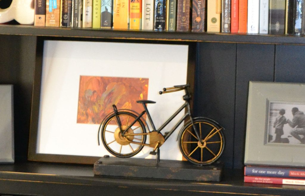 leaning a framed piece of artwork against the back of shelf to accessorize it and add depth