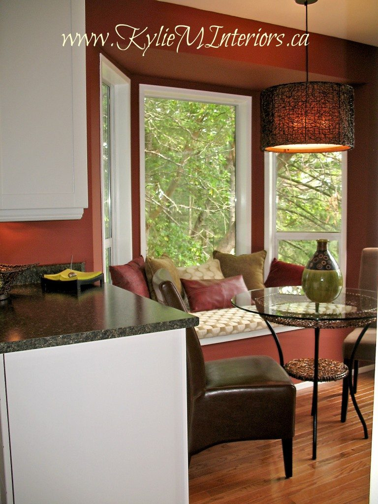 kitchen nook painted boxcar red by benjamin moore with white cabinets and bench seating area and oak floors