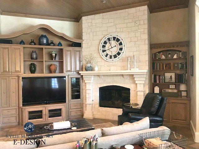 Limestone fireplace with wood ceiling and built-ins. Clock above mantel. Kylie M Interiors before photo, client photo