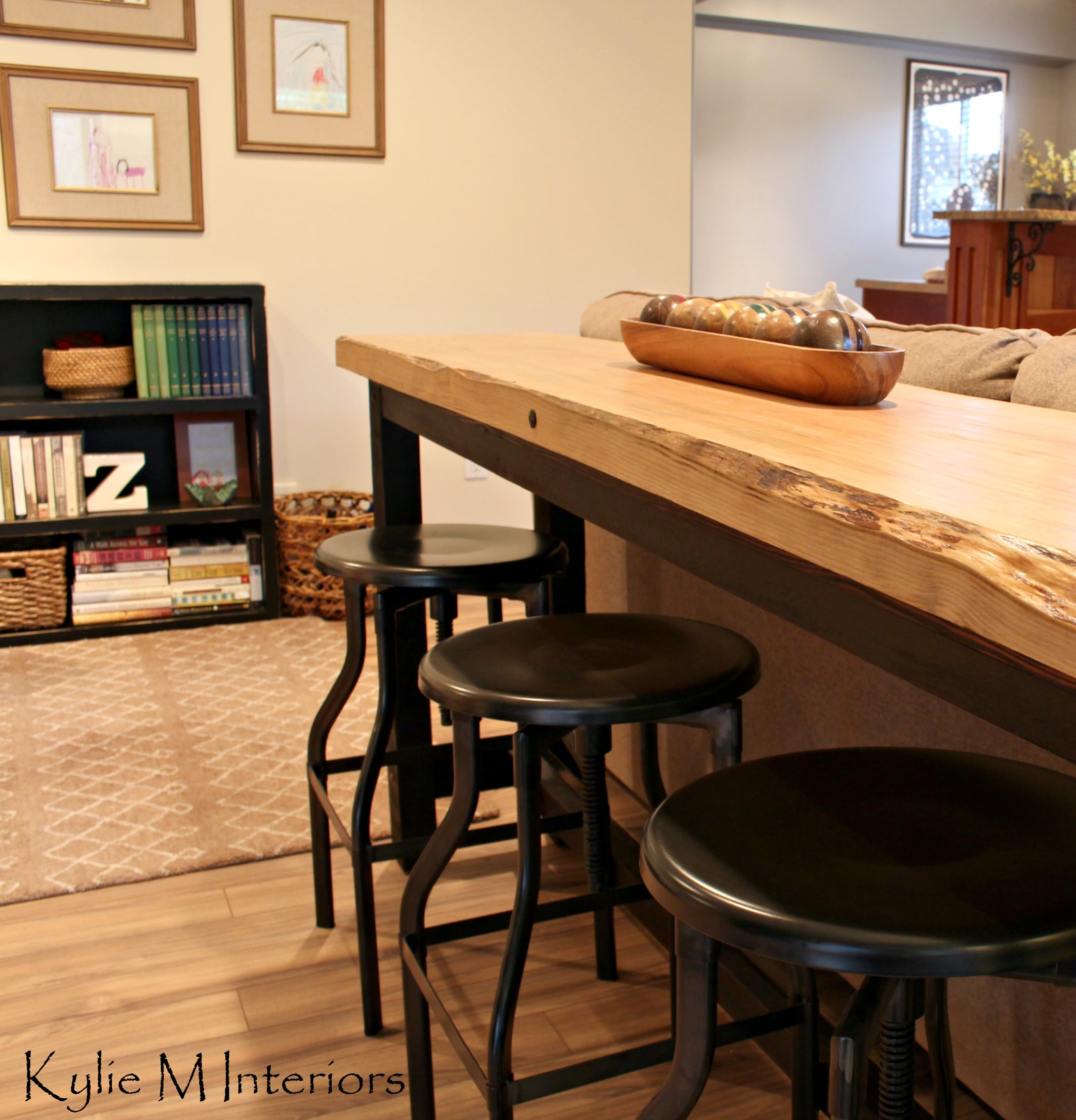 live edge bar table behind sectional with industrial stools in a man ...