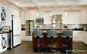 U shaped kitchen with island and raised bar top. Coffered ceilings, marble and black granite countertops and stainless steel. By Kylie M Interiors
