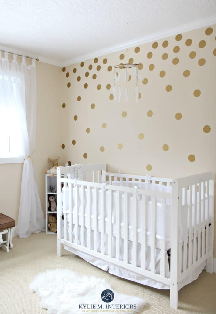Benjamin Moore Gentle Cream in a gender neutral baby nursery with gold polka dots and white crib. Kylie M Interiors