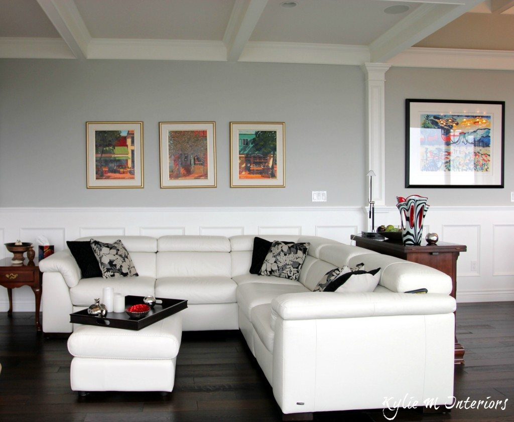 Best Benjamin Moore Gray paint color Stonington Gray shown with white leather sectional, dark wood floors and wainscoting