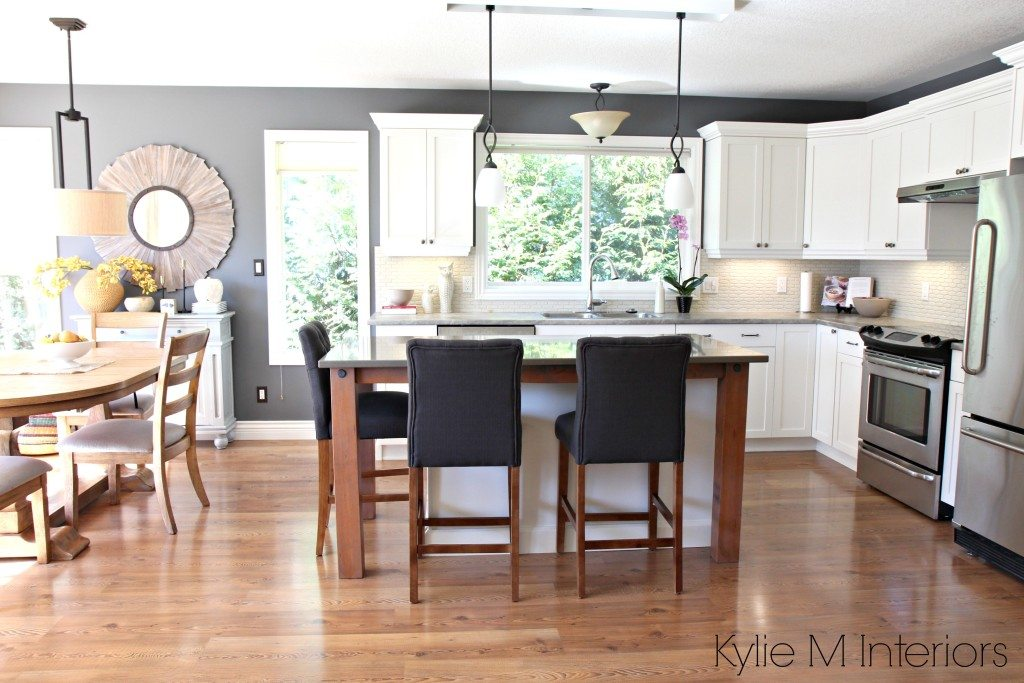 Open layout kitchen and dining, subtle country farmhouse style. Maple cabinets painted Cloud White, gray quartz, soapstone formica and rustic wood supports with stainless steel