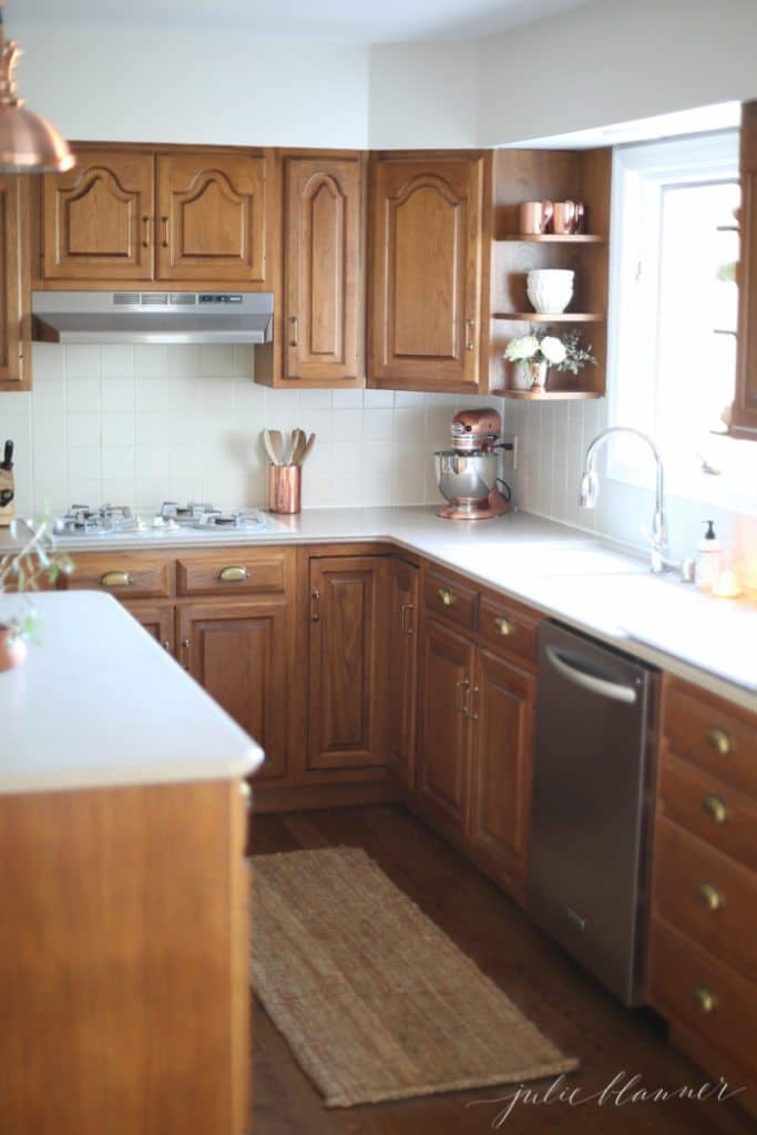 Ideas to update oak kitchen or bathroom cabinets without paint. Including hardware and decor. Design by Julie Blanner