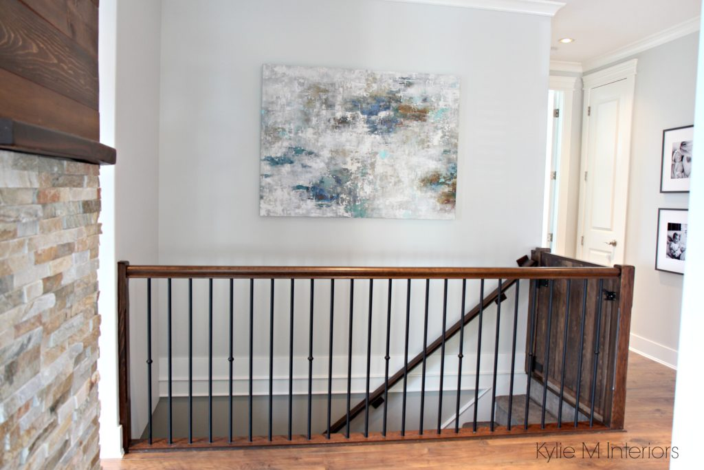 Benjamin Moore Gray Owl in hallway and stairwell with dark stained wood railing and artwork on wall. Kylie M Interiors E-design and online color consulting