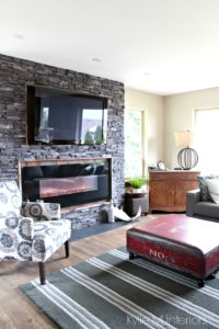 Black ledgestone fireplace surround with reclaimed wood around mounted tv. Unique coffee table trunk and home decor. Kylie M Interiors E-Design, Vancouver Island Colour Consultant