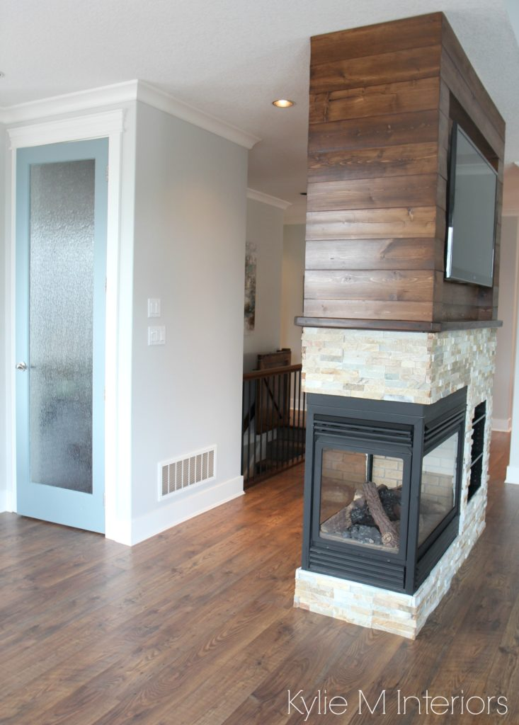 Pantry door painted Benjamin Moore Wedgewood Gray with Gray Owl walls. 3 sided fireplace with ledgestone and stained wood shiplap wall. Kylie M Interiors E-design and Online Color Consulting