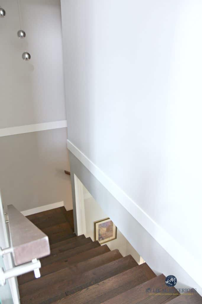 Stairway that is opened up to see into the wine room that is under the stairs. Wood stairs and gray walls. Kylie M Interiors Decorating and Design, E-decor services