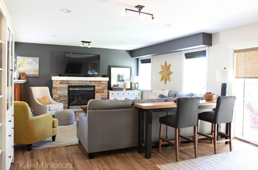 Family room decorating ideas with tv over stone fireplace, gold accents, Benjamin Moore Gray, sectional, live edge sofa table and stools by Kylie M Interiors e-design