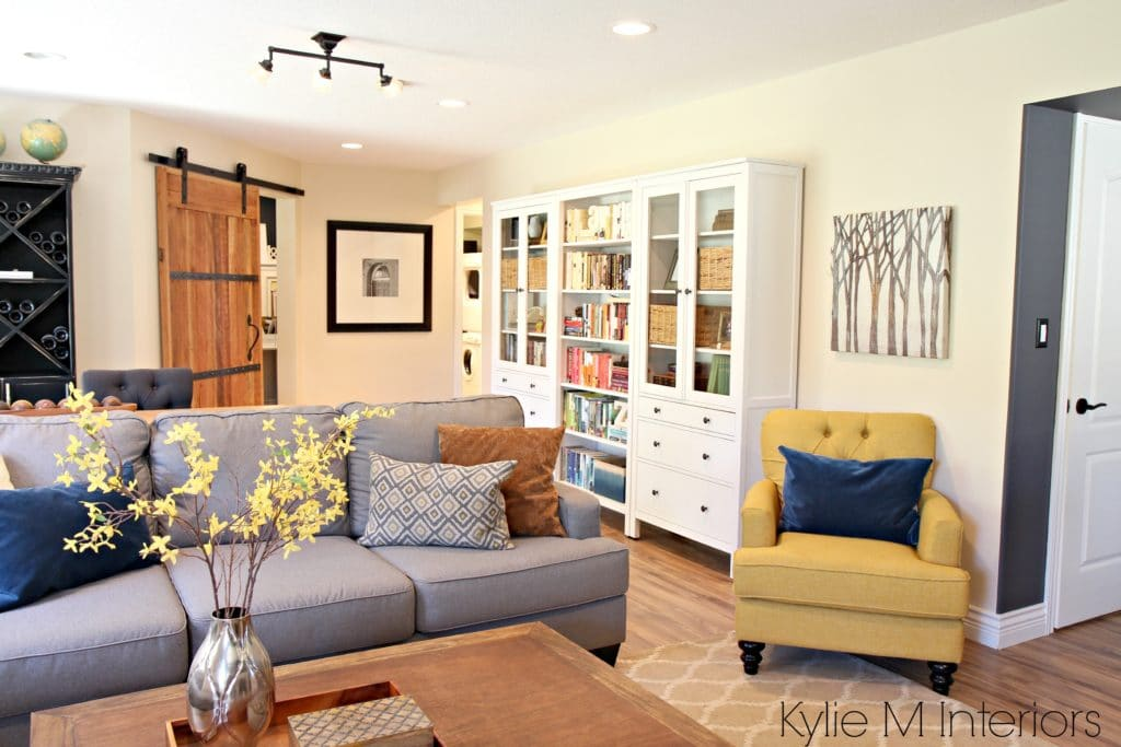 Family room with sliding farmhouse style barn door to home office, Ikea Hemnes bookcases and bookshelves, gray sectional and gold and chartreuse accents by Kylie M Interiors