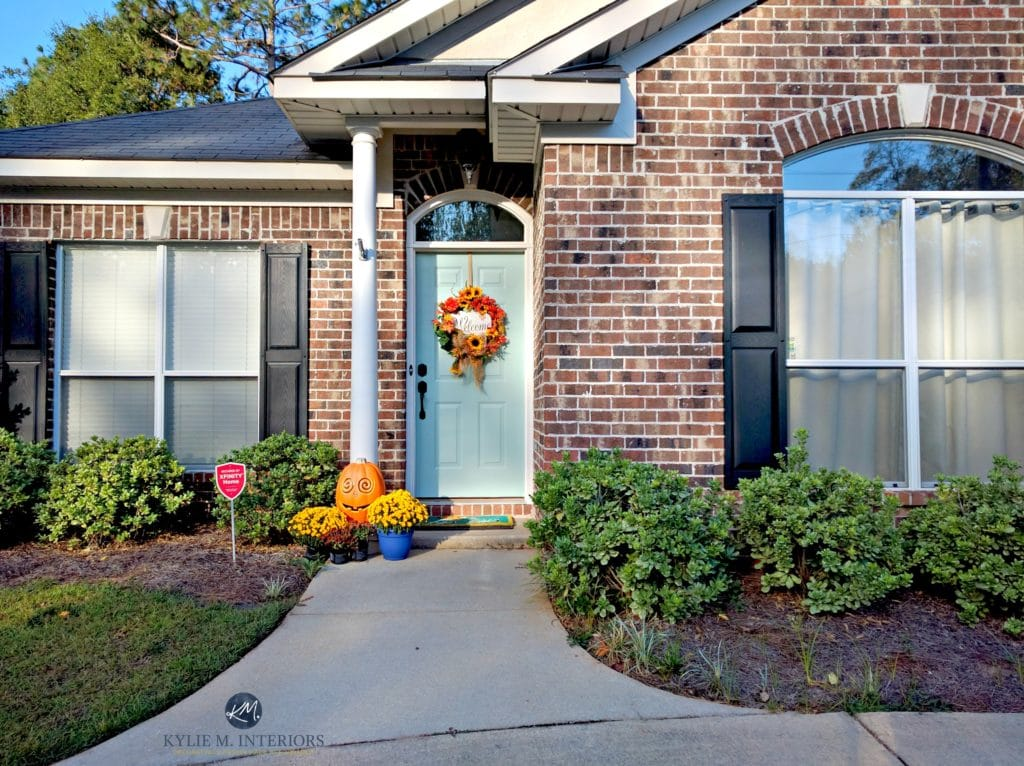Brick exterior with black shutters, greige trim and Benjamin Moore Wythe Blue front door. Kylie M Interiors E-design, Edecor and online color consulting