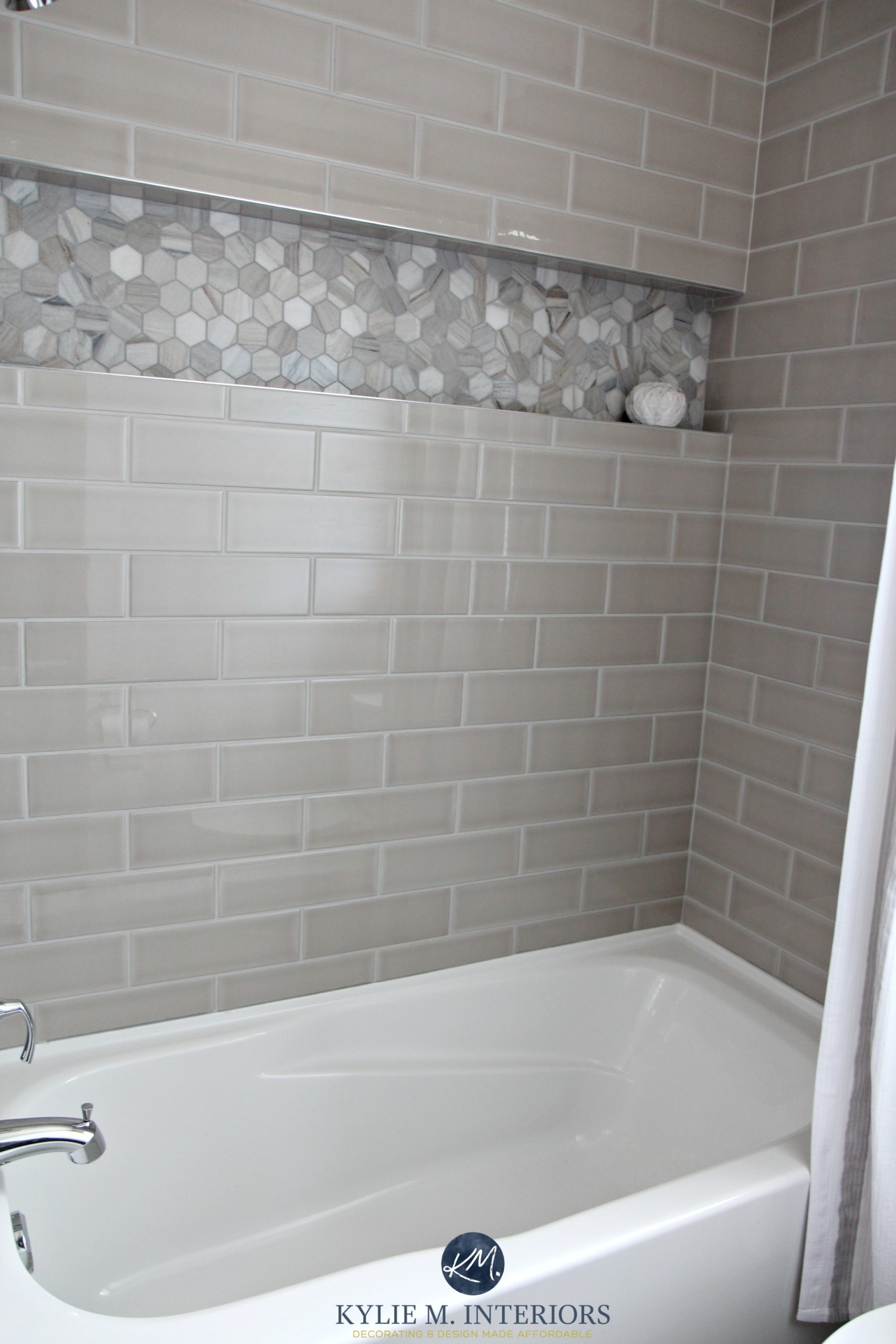 bathroom with bathtub and gray subway tile shower surround with niche or alcove in hexagon