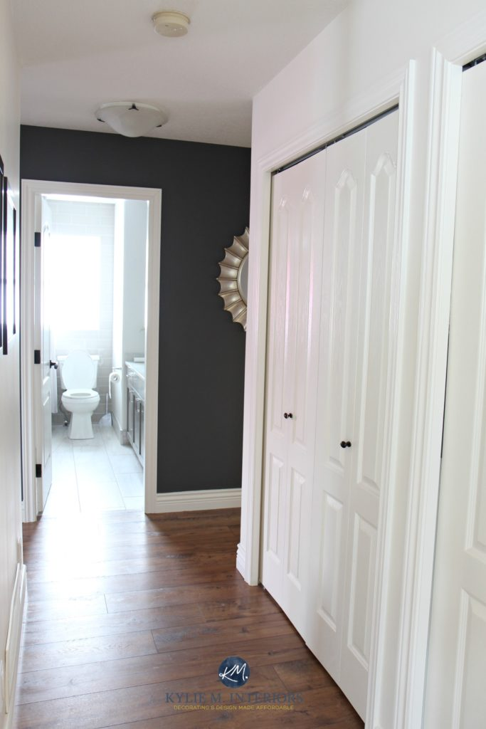 Hallway update with laminate wood look flooring, Benjamin Moore Gray feature wall, Sherwin Williams Creamy and door to bathroom. Kylie M INteriors E-design