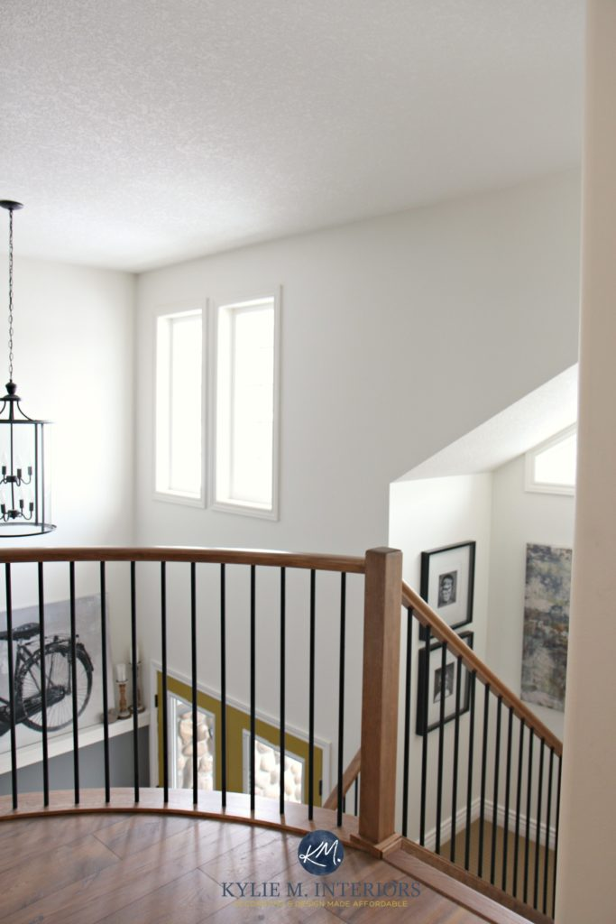 2 storey entryway, foyer and stairwell with rounded or curved wood and metal railing. Sherwin Williams Creamy
