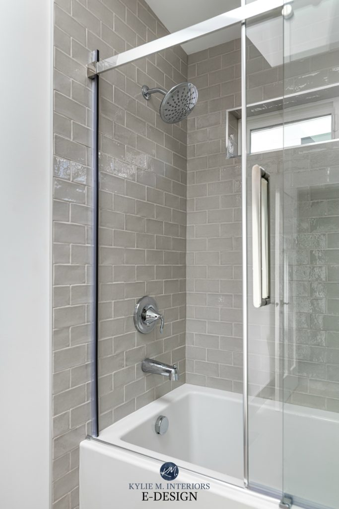 Bathroom, warm gray greige subway tile surround, light gray grout. Tub and shower with glass sliding door. Kylie M Interiors, E-design online paint colour consulting blog