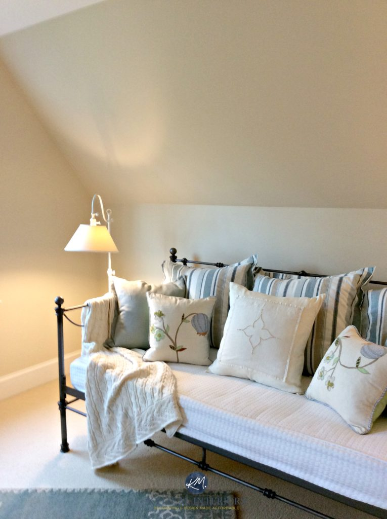 Benjamin Moore Gentle Cream in a guest bedroom wtih sloped ceilings and a day bed with blue accents. Kylie M Interiors E-design and Online Colour Consulting services. Expert color advice