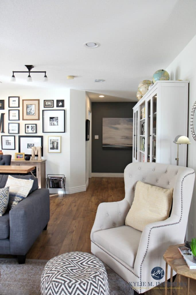 Family room with photo gallery wall, gray sectional. Sherwin Williams Creamy and Benjamin Gray feature wall. Hemnes bookcases and accent chair. Kylie M Interiors
