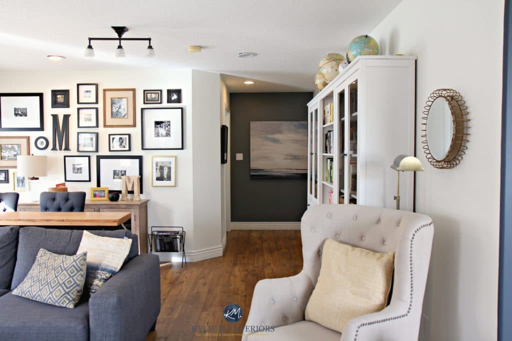 Family room with photo gallery wall, gray sectional. Sherwin Williams Creamy and Benjamin Gray feature wall. Hemnes bookcases. Kylie M Interiors