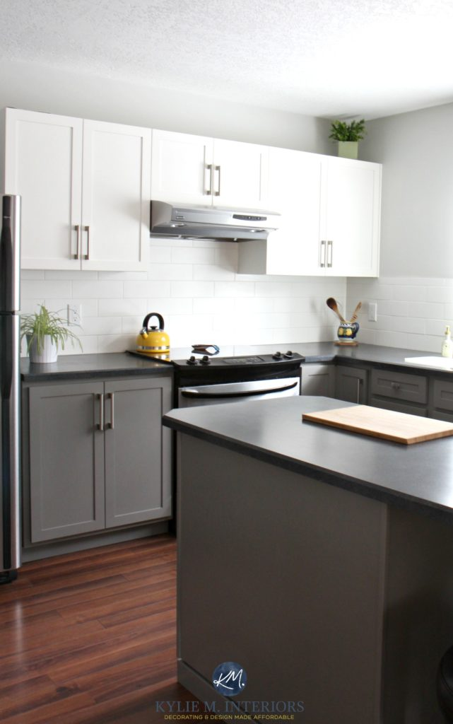 Painted kitchen cabinets with white and Benjamin Moore Chelsea Gray, Gray Owl, subway tile, red toned wood flooring and black laminate countertops. Kylie M Interiors E-design