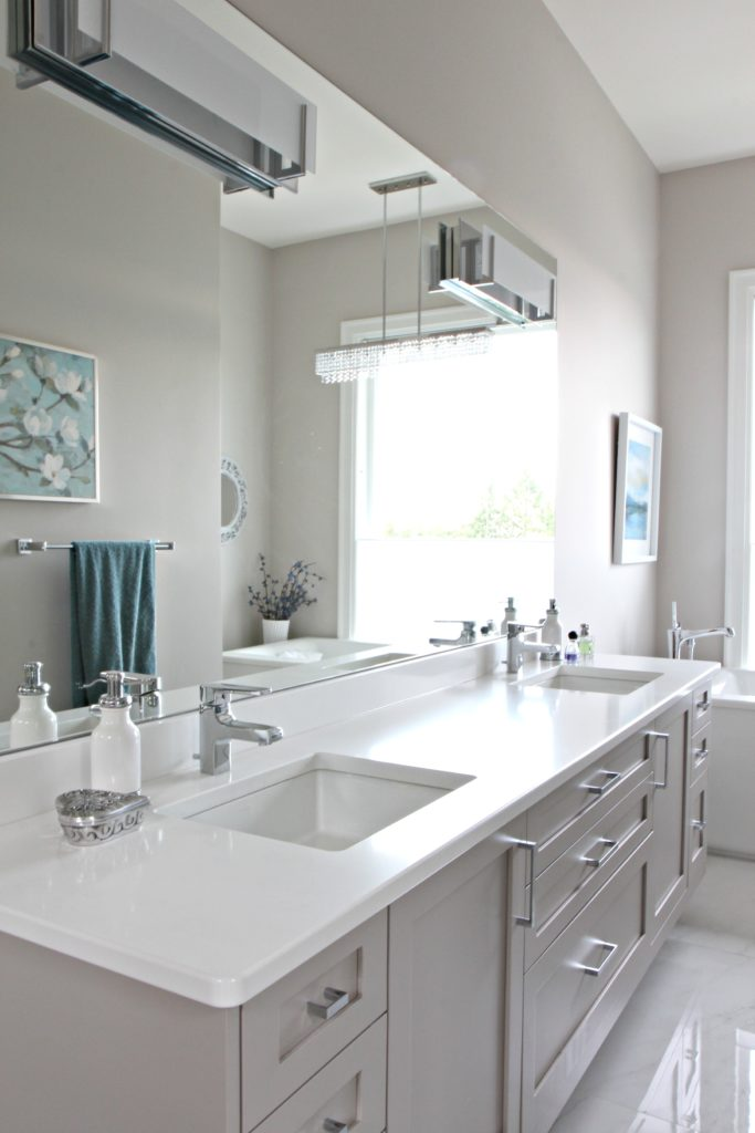 Bathroom with floating gray vanity, Cambria quartz countertop Kirkstead. Benjamin Moore Balboa Mist, large mirror. Kylie M Interiors Decorating and Design Online and Nanaimo