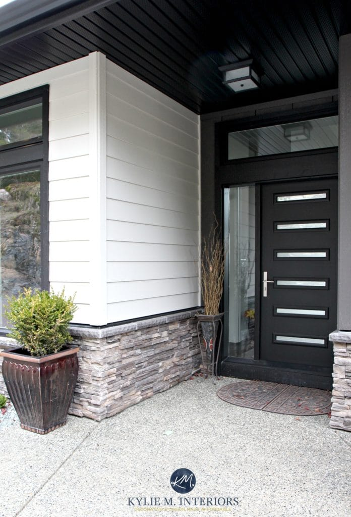 Contemporary exterior with James Hardi Cobblestone siding, black front door, soffits and stone. Kylie M INteriors E-design