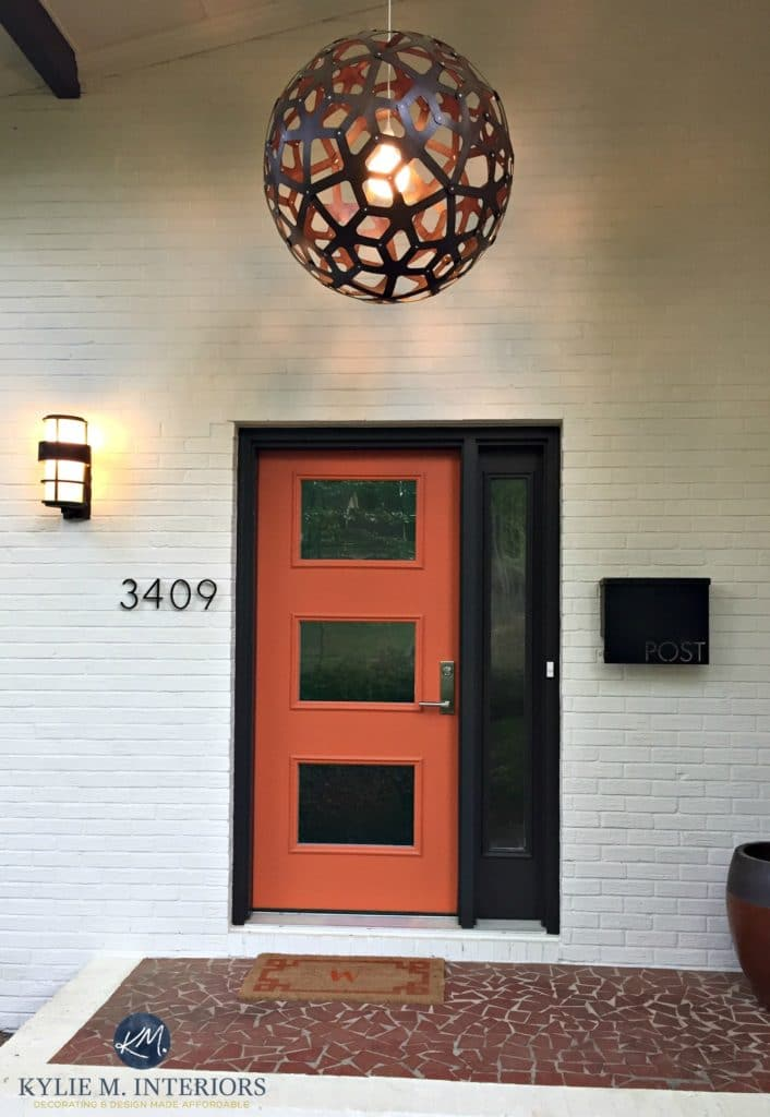 Exterior front door, mid century style painted orange with dark brown black trim and painted brick in a cream beige tone. Kylie M Interiors E-design and ONline Colour consulting decorating expert
