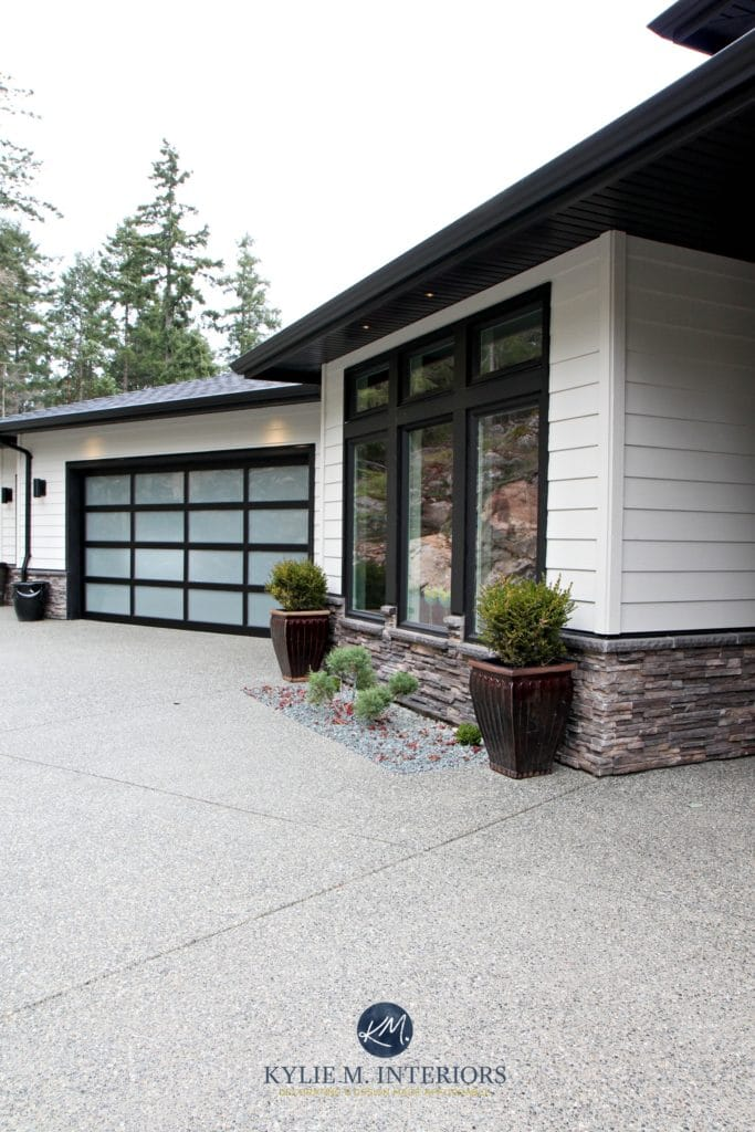 Hardiboard Cobblestone with black trim and stone exterior. Garage doors and black soffits. Kylie M Interiors
