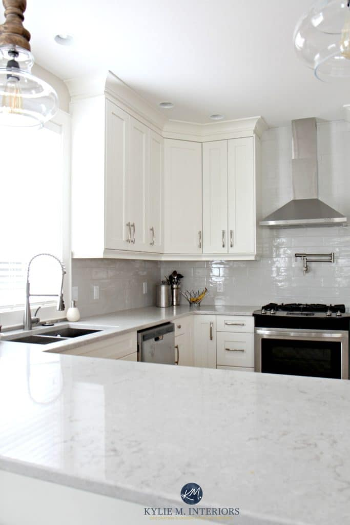 Low contrast white kitchen with Bianco Drift quartz countertops and gray subway tile backsplash. Kylie M Interiors