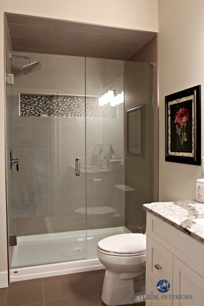 Small bathroom with walk in shower. Glass doors, fibreglass base, mosaic tile niche and large porcelain wall tiles. Sherwin Williams Worldly Gray. Kylie M Interiors