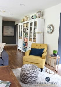 Ikea Hemnes bookcases in family room with chartreuse accent chair. Sherwin Williams Creamy paint color and home decor. Globe collection. Kylie M Interiors E-design