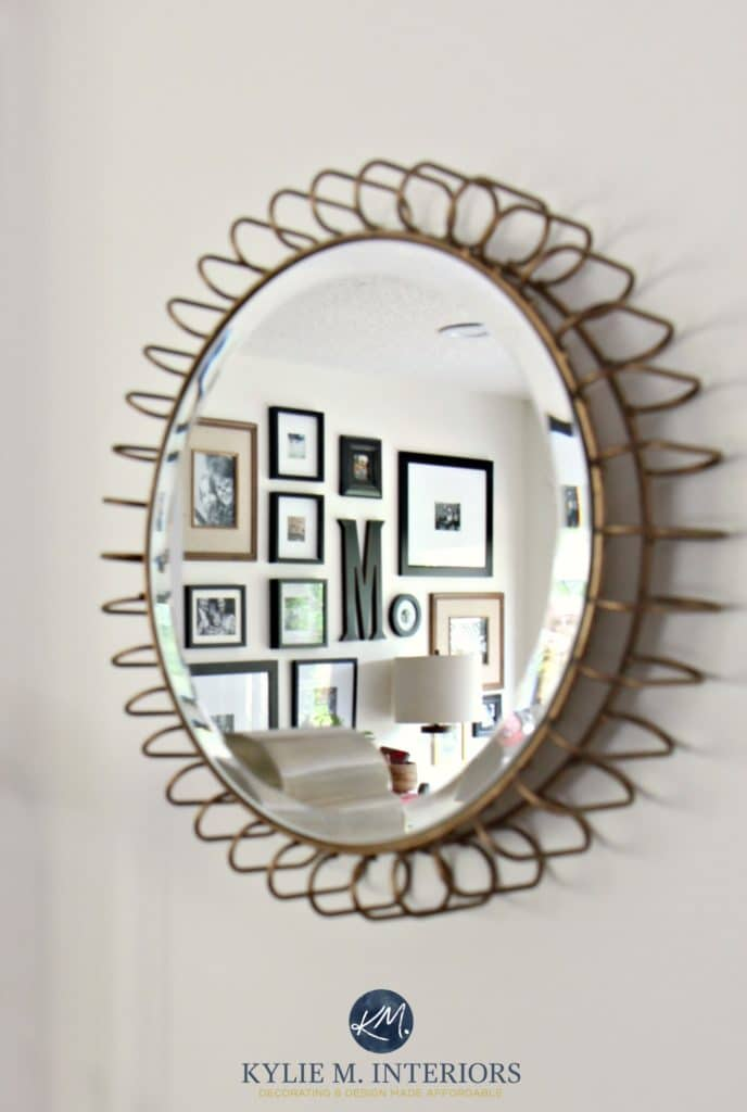Round accent mirror with gold detail reflecting photo gallery wall on Sherwin Williams Creamy. Kylie M Interiors E-decor and E-design. Color expert