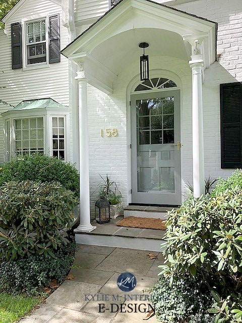 Aged copper roof, painted white brick exterior, black shutters and benjamin moore gray front door. Kylie M Interiors Edesign, online paint color consultant