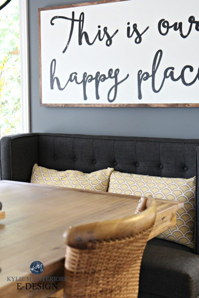 Large farmhouse wood sign in dining room. UPholstered bench, wood table. Kylie M E-design