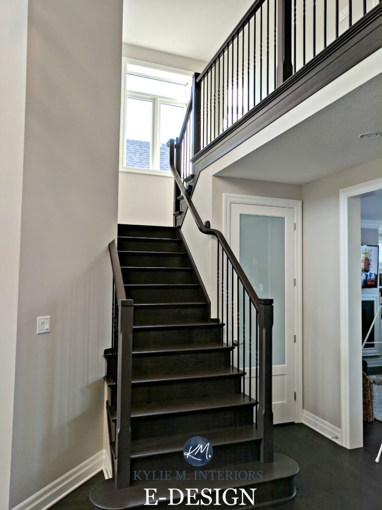Benjamin Moore Collingwood in a staircase with dark wood stair treads, black handrail. Kylie M INteriors E-design and online color consulting blog