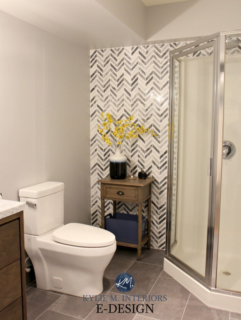 herringbone or chevron gray marble accent tile in small bathroom with corner shower feature wall. Kylie M interiors E-design