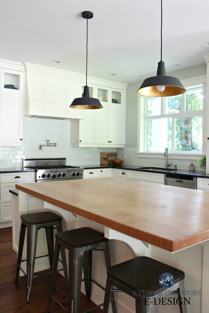 Kylie M Interiors Edesign. Butcher block island in farmhouse country style kitchen. Cloud White cabinets, subway tile backsplash. black and brass pendant lights