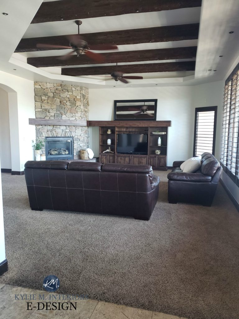 Living room with dark wood beams, trim and tv stand, stone fireplace, brown leather furniture and greige taupe