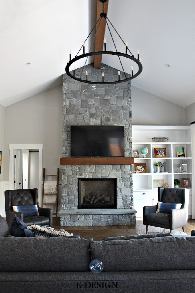 Living room, gray stone fireplace, round wheel chandelier, white built in bookcases, Stonington Gray paint colour. Kylie M Interiors Edesign, online paint color expert