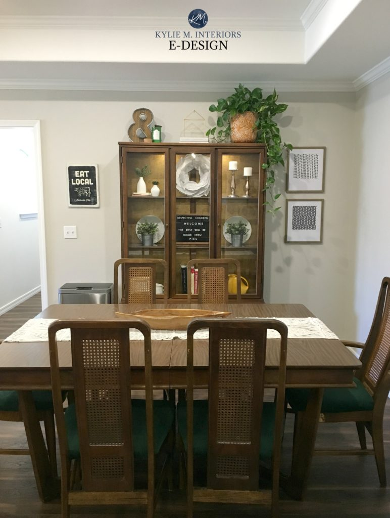 Dining room in Sherwin Williams Agreeable Gray, traditional style wood table and china cabinet with decor. Kylie M Interiors Edesign, online best paint color expert