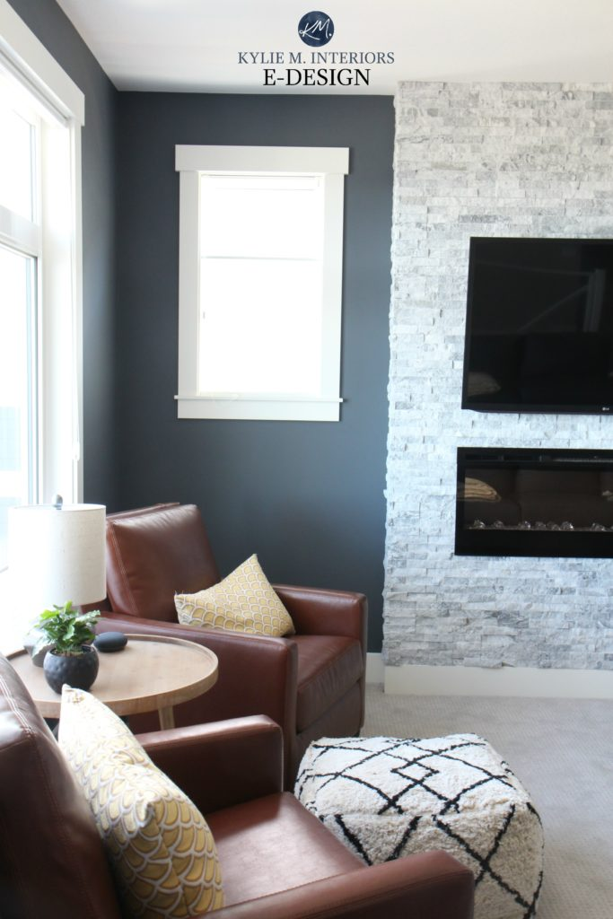 Benjamin Moore Anchor Gray, White Dove trim, travertine stacked stone fireplace, tobacco brown leather chairs, gray carpet. Kylie M Interiors E-design, online paint color consulting. Best blue paint