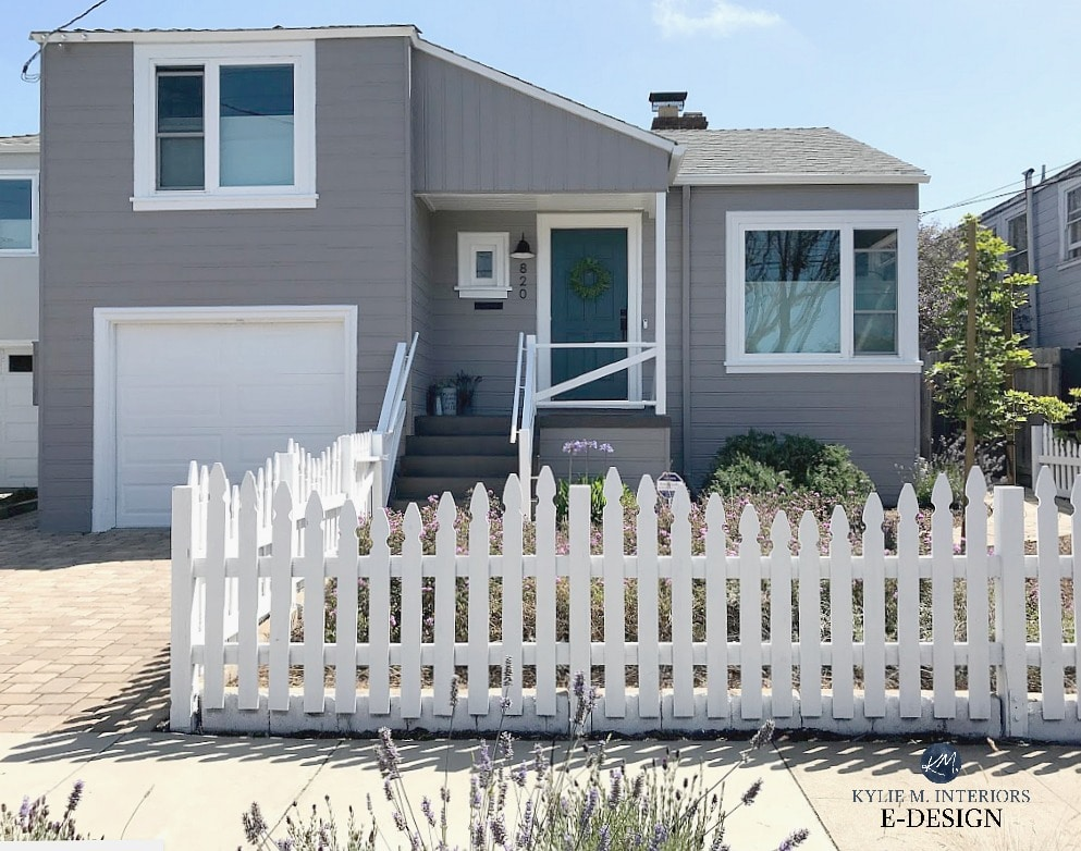 Exterior painted gray with purple undertone, blue green front door, Folkestone stairs, white picket fence and white trim and garage. Sherwin Williams Still Water, Polished Concrete siding, Pure White trim Kylie M Interiors Edesign, online paint colour consultation.