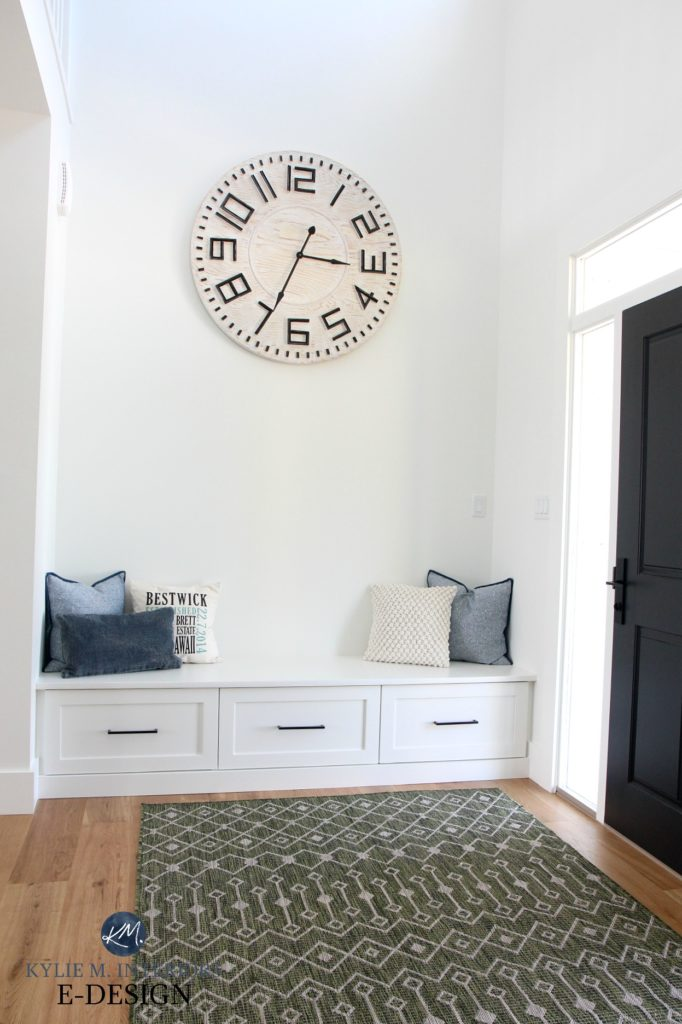 Kylie M Interiors EDESIGN. Entryway with vaulted ceiling, large oversized wall clock, builtin bench, painted black front door, Sherwin Williams Pure White walls, trim. Online paint colour advice blog
