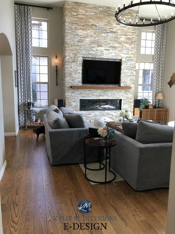 Popular gray or greige paint colour, Sherwin Williams Anew Gray, stacked stone fireplace, vaulted ceiling, oak floors, round chandelier. Kylie M INteriors Edesign, client photo